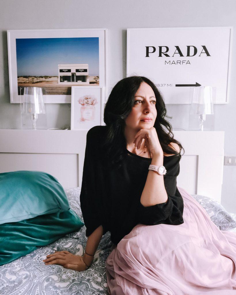 The Fashion Cherry Diary in camera seduta sul letto con alle spalle due poster Desenio con Prada Marfa gonna in tulle lunga rosa